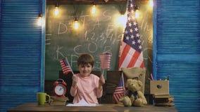 Pojke i klassrumet som vinkar USA-flaggor på bakgrund av skolförvaltningen och den stora flaggan av USA Lyckligt vinka för litet  arkivfilmer
