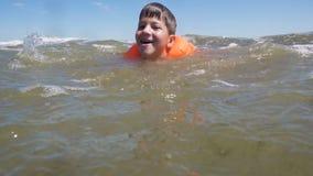 Pojke i lifejacketbad i havet med vågor lager videofilmer