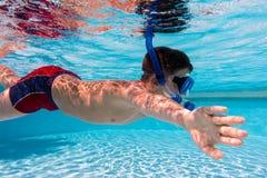 Pojke i maskeringsdyk i simbassäng arkivbilder