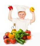 Pojke i matlagninghatt med isolerade grönsaker Arkivbilder