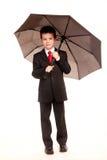 Pojke i official dresscode med ett paraply Fotografering för Bildbyråer