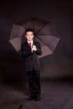 Pojke i official dresscode med ett paraply Arkivbilder