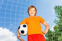 Pojke i orange T-tröja med fotboll nära träverk arkivbild