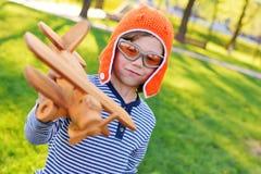 Pojke i pilot- spela för orange hjälm i leksaktränivå mot gräsbakgrund arkivbild