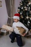 Pojke i röd hatt för jultomten med gåvor Arkivbilder