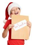 Pojke i röd hatt med bokstaven till santa - begrepp för jul för vinterferie Arkivbilder