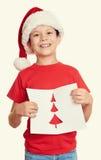 Pojke i röd hatt med bokstaven till santa - begrepp för jul för vinterferie Arkivbild