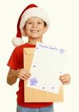 Pojke i röd hatt med bokstaven till santa - begreppet för jul för vinterferie, gulnar tonat Royaltyfri Fotografi