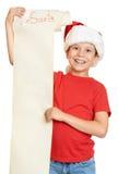 Pojke i röd hatt med den långa snirkelbokstaven med önska till santa Arkivfoton