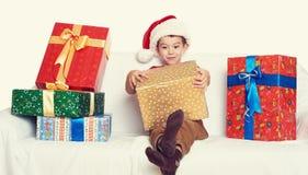 Pojke i röd santa hjälpredahatt med gåvaaskar - jul semestrar begrepp Arkivfoto