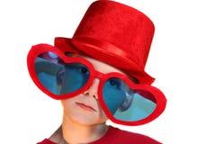 Pojke i röda horisontalhatt- och hjärtaexponeringsglas Royaltyfria Bilder