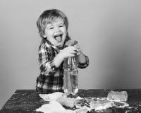 Pojke i rutig skjorta på blå bakgrund Litet hjälpredabegrepp för föräldrar Unge med att skratta framsidahållsprej Arkivbilder