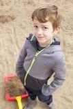 Pojke i sandlådan som spelar med sand Fotografering för Bildbyråer