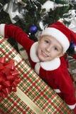 Pojke i Santa Claus Outfit Holding Christmas Present Royaltyfri Foto