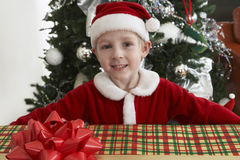 Pojke i Santa Claus Outfit Holding Gift Arkivbild