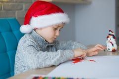 Pojke i Santa Claus som drar en pastellfärgad teckning för Santa Claus Fotografering för Bildbyråer