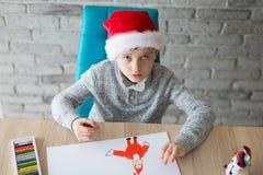 Pojke i Santa Claus som drar en pastellfärgad teckning för Santa Claus Royaltyfria Bilder