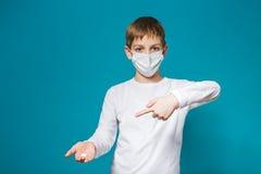 Pojke i skyddsmaskering som pekar på preventivpiller Arkivfoto