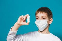 Pojke i skyddsmaskeringen som ser preventivpillerar Arkivfoto