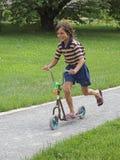 Pojke i sparkcykeln arkivbild