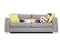 Pojke i sportswear med en fotbollboll som sover på en modern soffa Arkivfoto