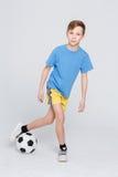 Pojke i tillfälligt med fotbollbollen på vit studiobakgrund Arkivbild