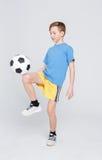 Pojke i tillfälligt med fotbollbollen på vit studiobakgrund Royaltyfria Bilder