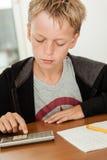Pojke i tröja genom att använda räknemaskinen för att kontrollera hans arbete Arkivbild