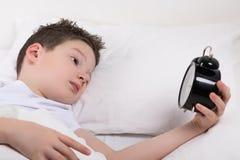 Pojke i vit säng som för ett tag ser med ett öga i ringklockan arkivfoton