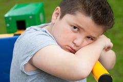 Pojke ledset, fett som är överviktig, övning som tröttas, blick, stående, instruktör, unge Arkivfoton