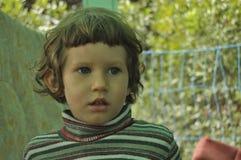 pojke little stående Ett barn med lockigt hår Royaltyfria Foton