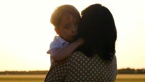 pojke little st?ende Solens strålar trycker på barnets framsida och att omfamna hans moder och son som erfar sinnesrörelser av lager videofilmer