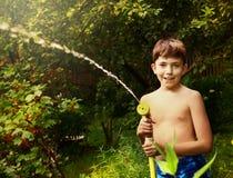 pojke med att bevattna röret på den gröna trädgårds- bakgrunden Arkivbilder