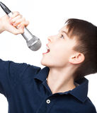 Pojke med att sjunga för mikrofon Arkivfoto