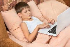 Pojke med bärbara datorn i säng royaltyfria foton