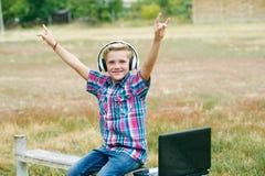 Pojke med bärbara datorn och hörlurar som ska göras utomhus Arkivbild