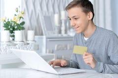 Pojke med bärbara datorn och kreditkorten Royaltyfria Bilder