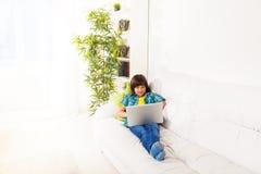 Pojke med bärbara datorn på soffan Arkivfoto