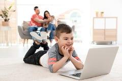 Pojke med bärbara datorn som ligger på matta nära hans familj arkivbilder