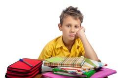 Pojke med böcker som ser borrade Alla på vit bakgrund Fotografering för Bildbyråer