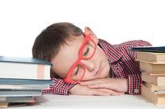 Pojke med böcker som sover på tabellen Arkivfoton