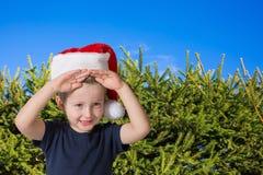 Pojke med blåa ögon i ett rött lock Arkivbild