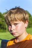 Pojke med blont hår som ser allvarligt Arkivfoto