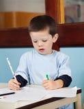 Pojke med blyertspennateckningen på papper i klassrum Fotografering för Bildbyråer