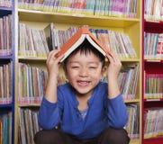 Pojke med boken på hans huvud arkivbild