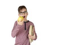 Pojke med bunten av böcker under hans arm som äter ett äpple fotografering för bildbyråer
