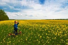 Pojke med cykeln på landsfält med blommor i solig dag Royaltyfria Bilder