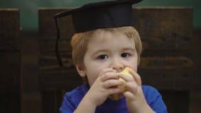 Pojke med den doktorand- hatten och äpplet l?ra f?r begrepp Skolbarn i likformig L?rare och deltagare tillbaka skola till lager videofilmer
