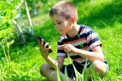 Pojke med den mobila telefonen Arkivfoton