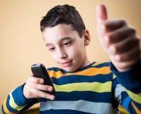 Pojke med den mobila telefonen Royaltyfri Bild